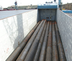 42m / 30 tonne Steel Pilings ready to be discharged, sorted and reloaded to barges.
